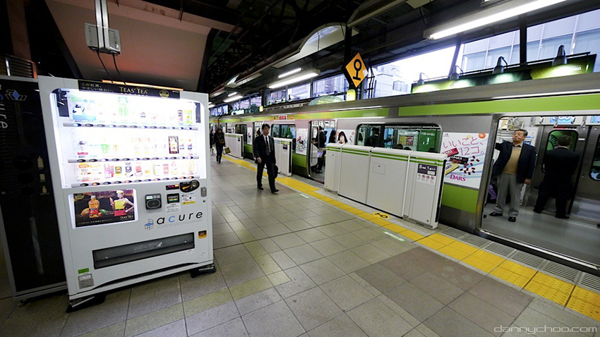 A view of the Tokyo subway system, with a yellow band running across the platform floor, denoting a slightly raised divet warning blind people that the platform ends there